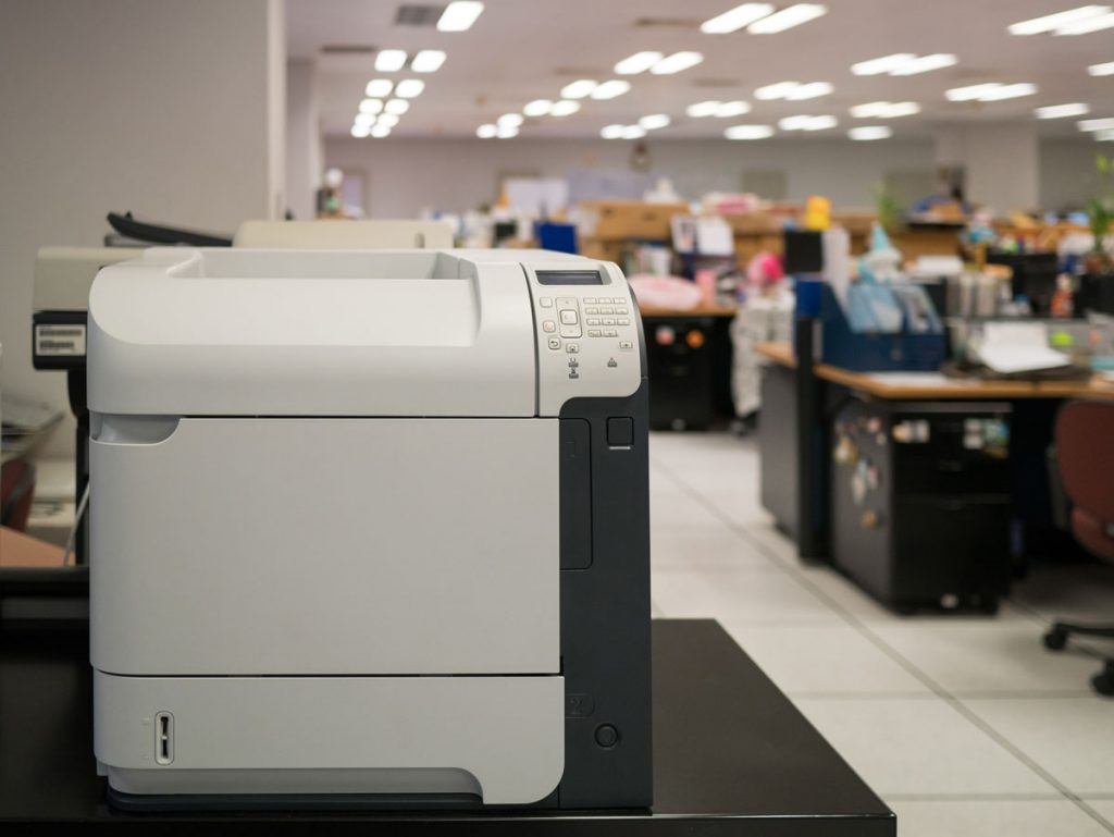 Multifunction printer sitting in a busy office printer