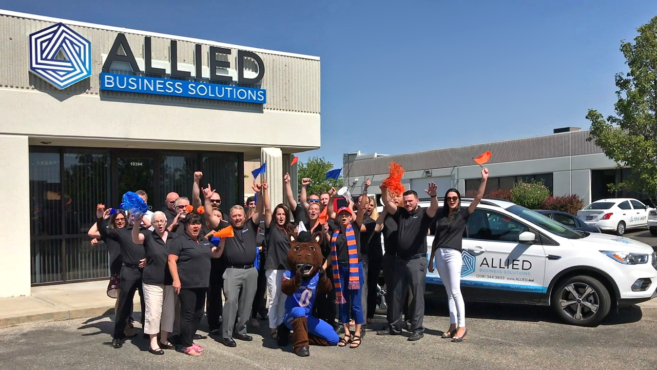 Buster Bronco and Allied employees raising hands and waving in front of Allied Business Solutions building